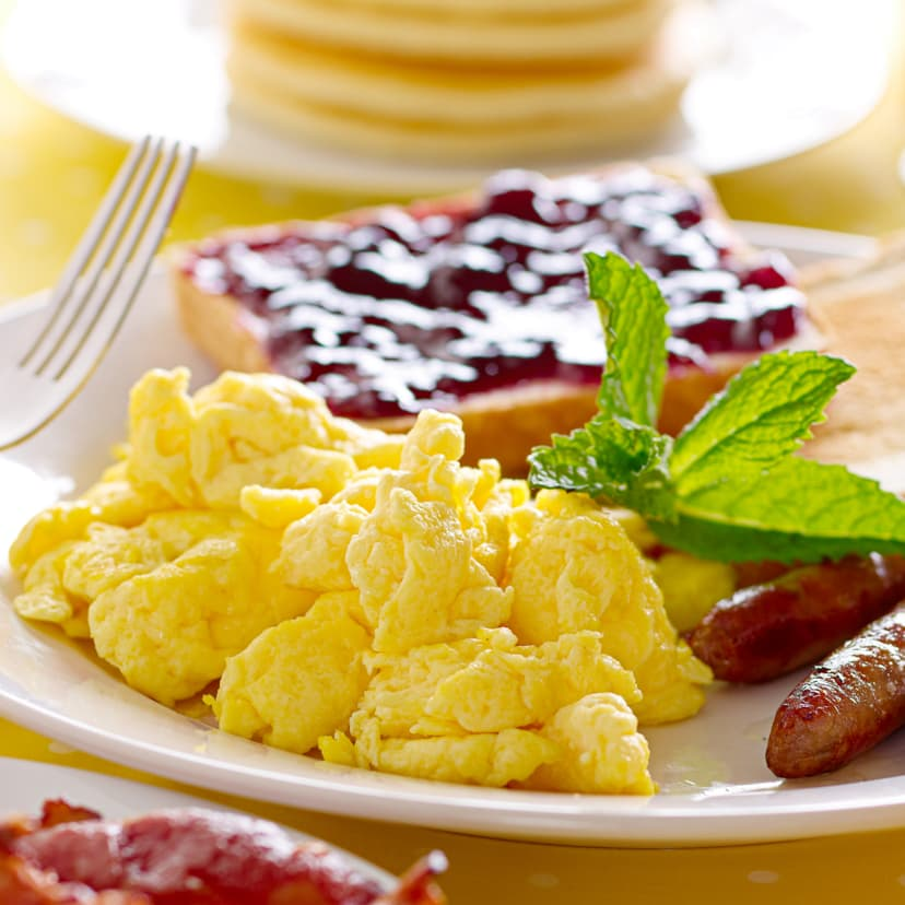 Scrambled eggs, sausage links, and toast served with orange juice