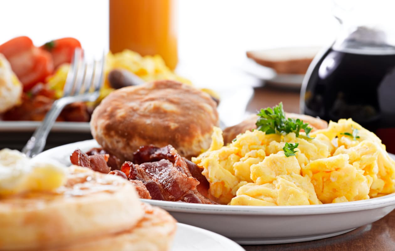 Scrambled eggs, bacon, and biscuit served with orange juice
