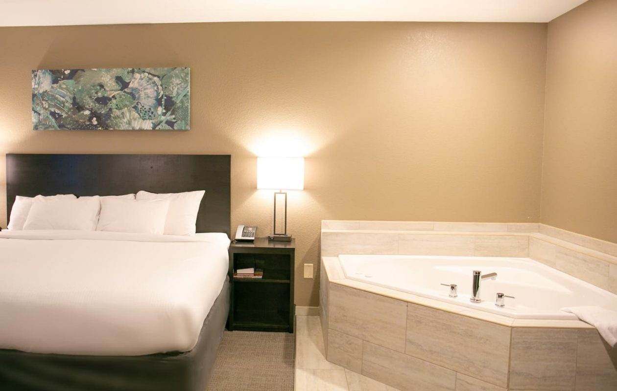 A king bed with a jetted tub next to it