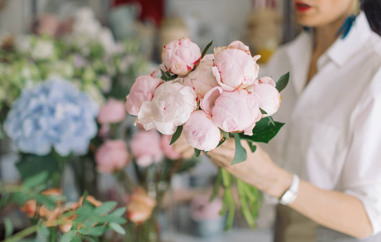 A florist works with a bouquet of flowers