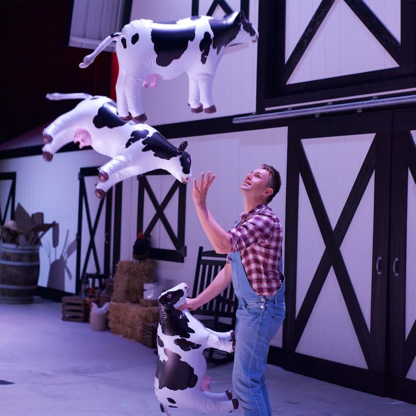 Man juggling three plastic cows on stage