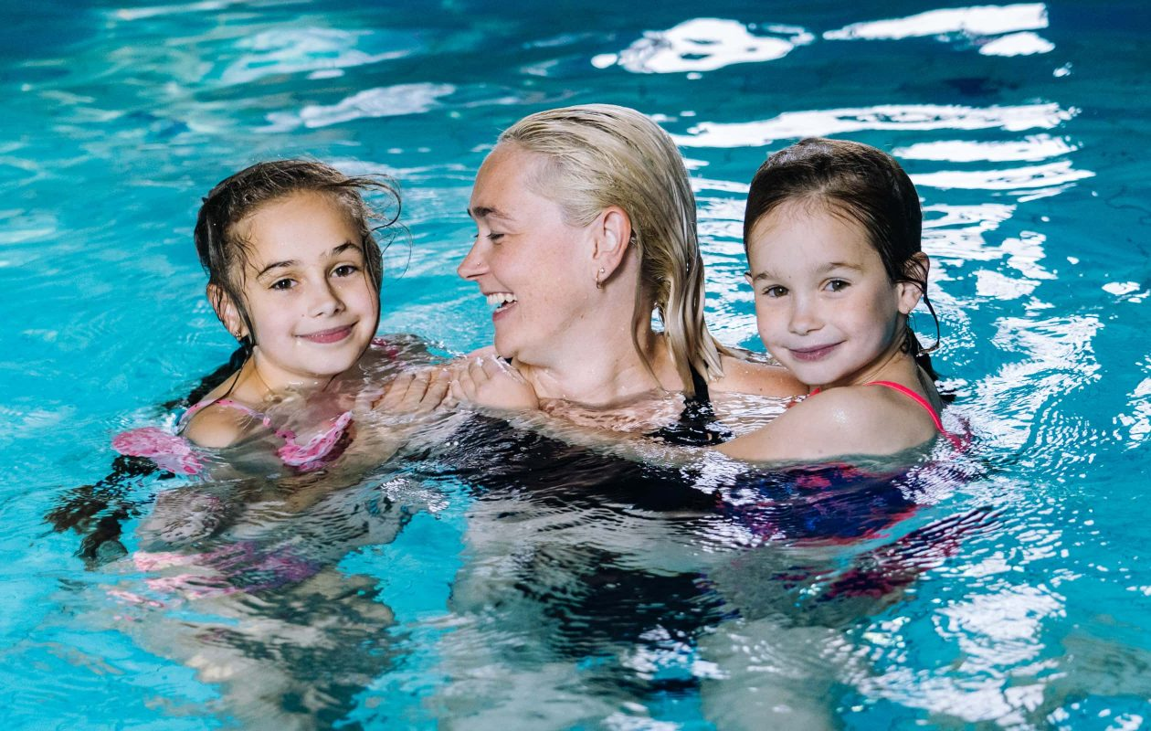 Mother swimming with her two daughters in an indoor pool