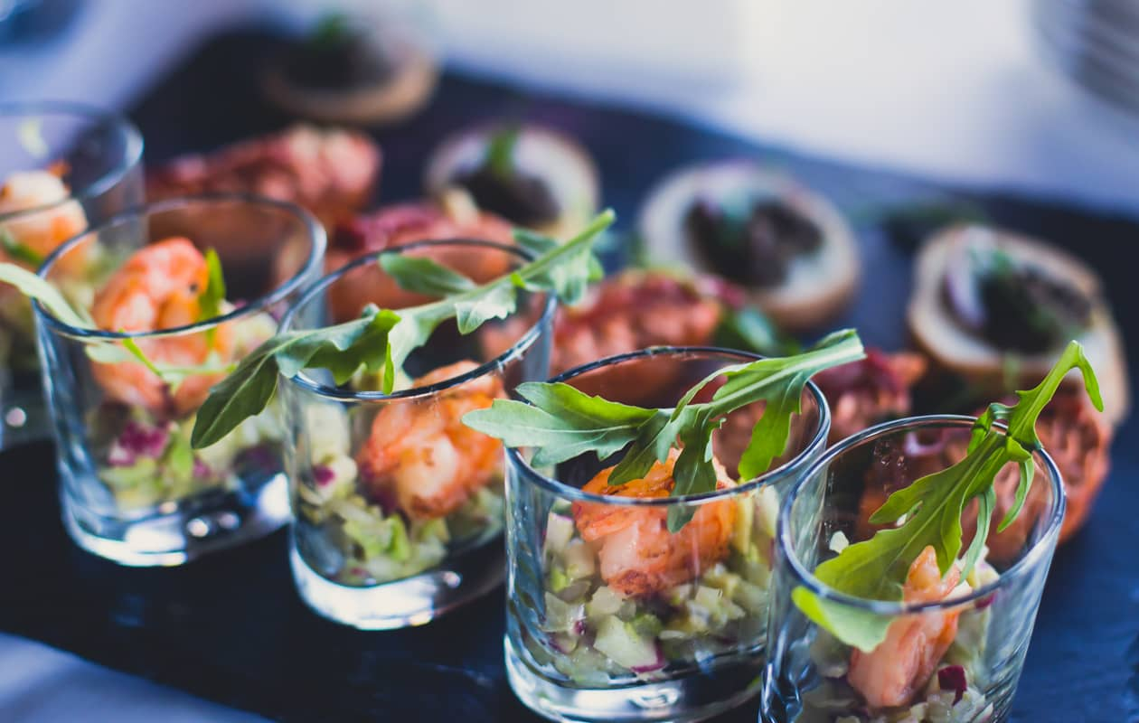 Shrimp appetizer in a shot glass served with local greens